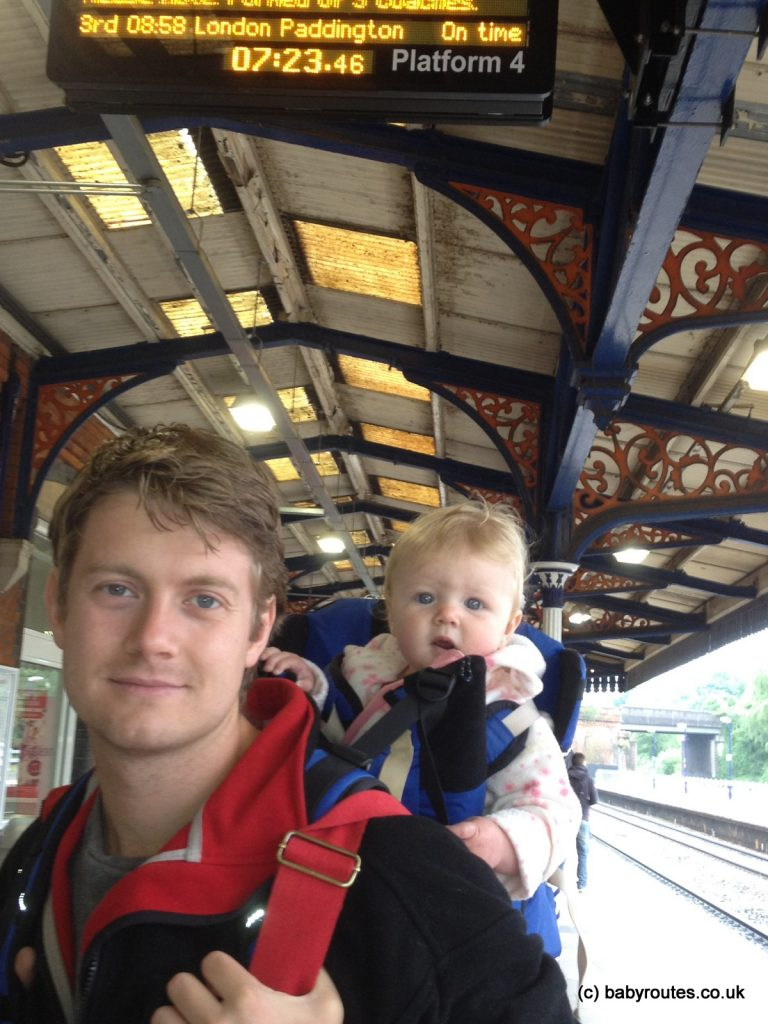 Travelling across London with children - photo of baby in carrier at train station.