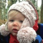 Baby wearing wooly pink hat with ear warmers.