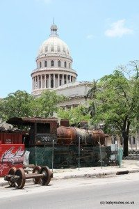 A capital of contrasts: El Capitolio towers grandly over a yard full of rusty disused trains in Old Havana